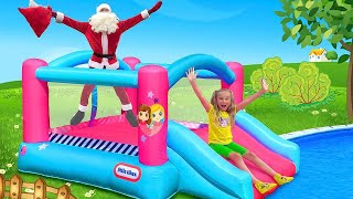 Sasha and Max descend from the water slide with Santa