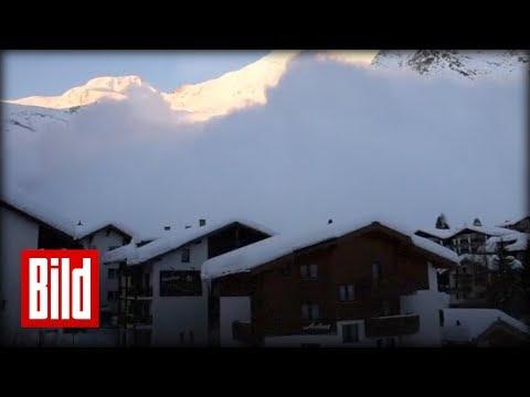 Schnee-Lawine hüllt gleich ein ganzes Dorf in den Alpen ein