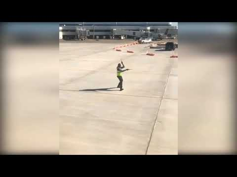 Airport employee dancing on tarmac to -spirit in the sky  by Norman GreenBaum
