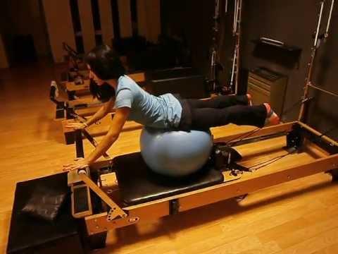 Ejercicio de pilates con pelota sobre reformer | Rebeca Ludman