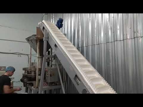 Подающий конвейер с  накопительным  вибробункером, лента с гофробортом и толкателями.