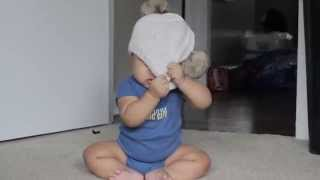 Baby struggles to take off hat