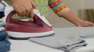 Indian women ironing the clothes with a steam iron