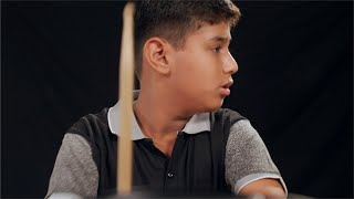 Shot of a young Indian boy playing red drums