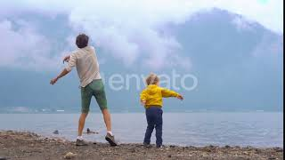 Shot of a Father and Son Throwing Stones Into the Bratan Lake in Highlands of the Bali Island |