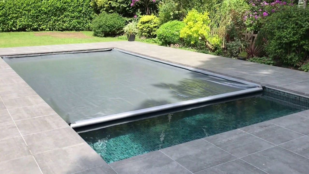 Aquamatic swimming pool safety cover with Hidden Leading Edge Bar Lid system