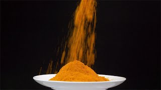 Pile of turmeric powder in a shiny white plate isolated over black background