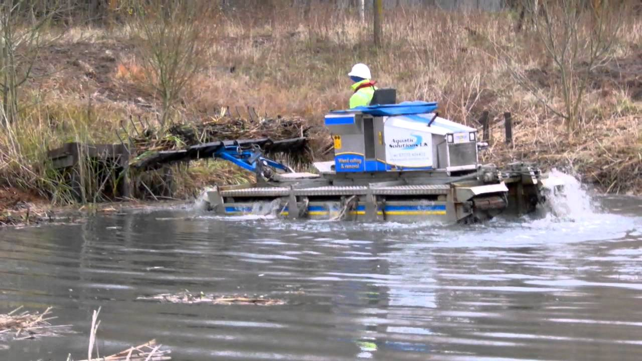 Truxor Excavator And Clearing Rake Cleaning The Lake At