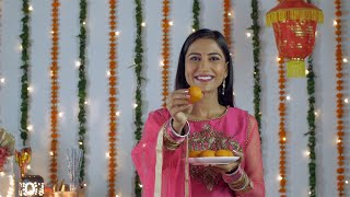 Attractive Indian woman happily smiling and showing sweets to the camera - Diwali festival