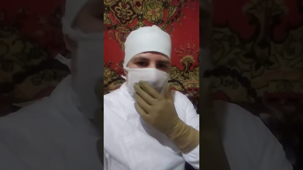 In the image of a Surgeon in a white surgical gown in a white mask with a  cap and brown rubber glove