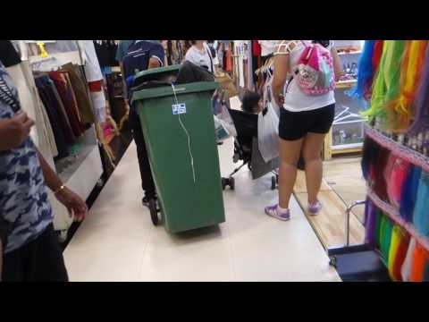 Man wheeling a garbage bin in a shopping mall in Prathunam, Bangkok