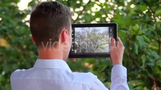 Stock Footage - Teen Taking Pictures Of Nature Scenes With His Pad   VideoHive