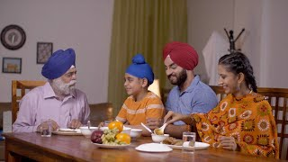 Happy Sikh Indian family eating together at home - family concept. Grandfather, father, mother, and grandson
