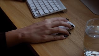 Closeup shot of woman's hand working with wireless mouse in office
