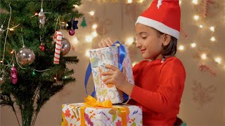 Christmas Evening - Adorable little girl wearing Santa hat opening her Christmas gifts