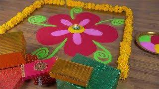 High angle shot of a colorful rangoli decorated with flowers, Diyas and Diwali gifts - Diwali festival