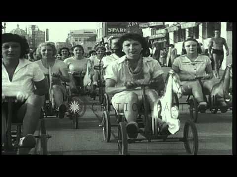 Women race on mechanical hobby-horse race at Santa Monica, California. HD Stock Footage