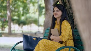 Attractive Indian lady spending her leisure time in a park while reading a book