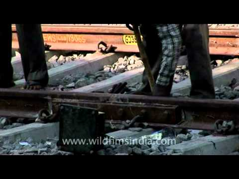 Installing and repairing Indian railway track at a small railway station in India