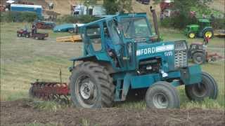 2WD Ford tractor fighting to pull plough up steep hill