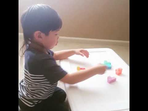 3 year old Dez building a cube from shapes