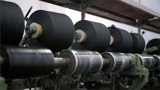 Black yarn spools running on the machine in textile factory