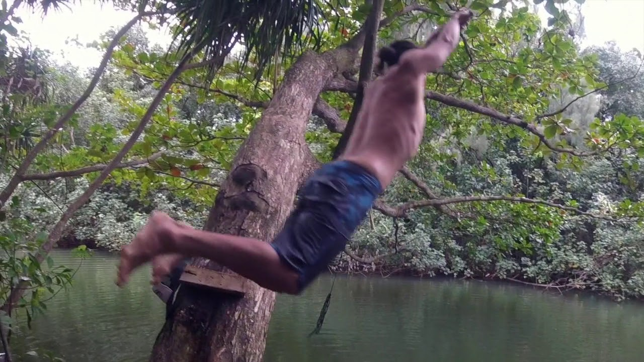 Someone Hanging Onto The Rope Swing About To Make A Big Splash In Plunge Pool