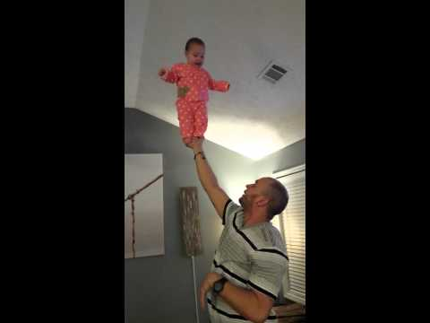 6 month old future gymnast standing on Dad's hands