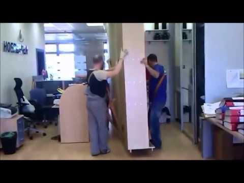 Профессиональные грузчики переносят очень тяжелый шкаф