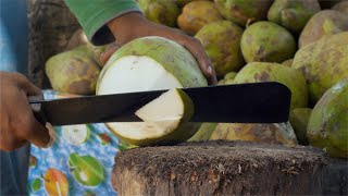Closeup shot of an Indian vendor's hands cutting a coconut using a big knife