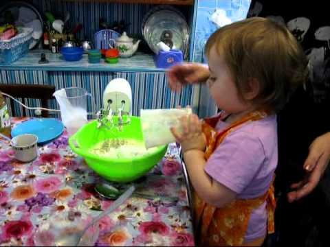 Детский фартук. Ребенок в год и три месяца готовит кексы.