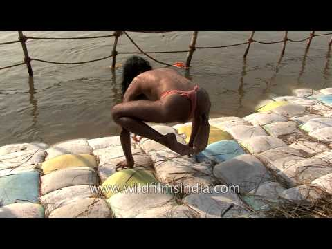 Only in India: Sadhu does yoga on sand bags on Ganges bank, standing on fingers alone!