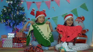 Cute little children opening their Christmas gifts while sitting near a decorated Christmas tree