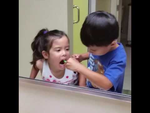 Big Brother Helps Little Sister Brush Teeth