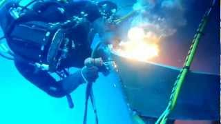 commercial diver burning off damaged steel plate underwater using broco oxy thermic torch