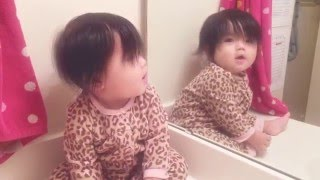 Cute baby looking at own reflection
