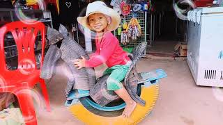 Kid enjoys riding horse / tire horse handmade in cambodia