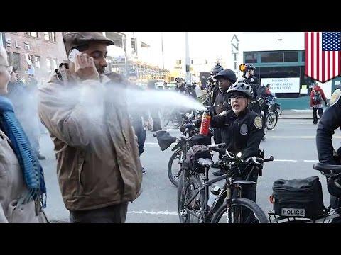 Policjantka używa gazu pieprzowego na przechodniu