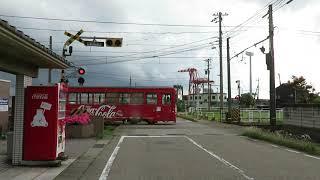 2019年06月11日 万葉線 越ノ潟駅を発車して踏切を渡るデ7075