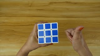 Closeup shot - Indian female playing with a Rubik's cube against a wooden table