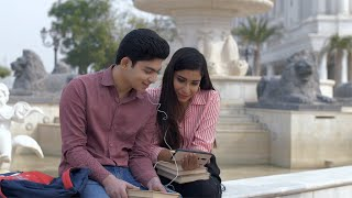 Cute Indian college couple enjoying watching movie together on a smartphone