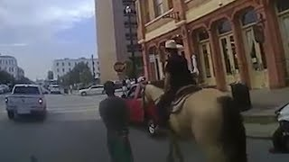 Bodycam footage of mounted officers leading man down the street in handcuffs