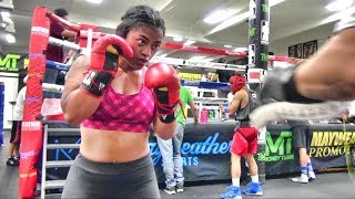 Young lady learning boxing hitting the pads inside the Mayweather Boxing Club