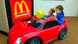Katy and Max drivig by ride on cars and horse to McDrive for Happy Meal in McDonalds