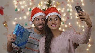 Attractive happy young Indian couple taking the selfie with Christmas gift