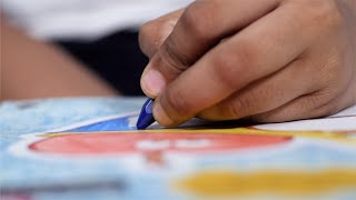 Closeup shot of an Indian child / kid coloring with a blue crayon in his drawing book