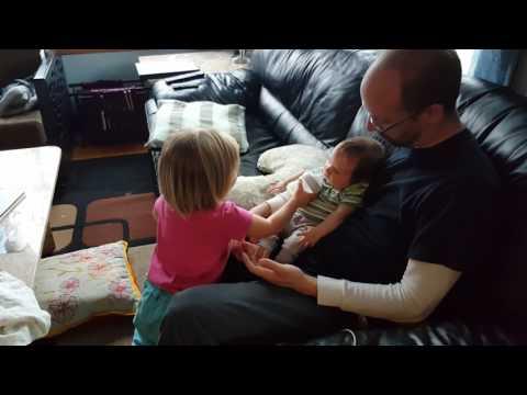 Mackenzie helps Mason learn to take a bottle.