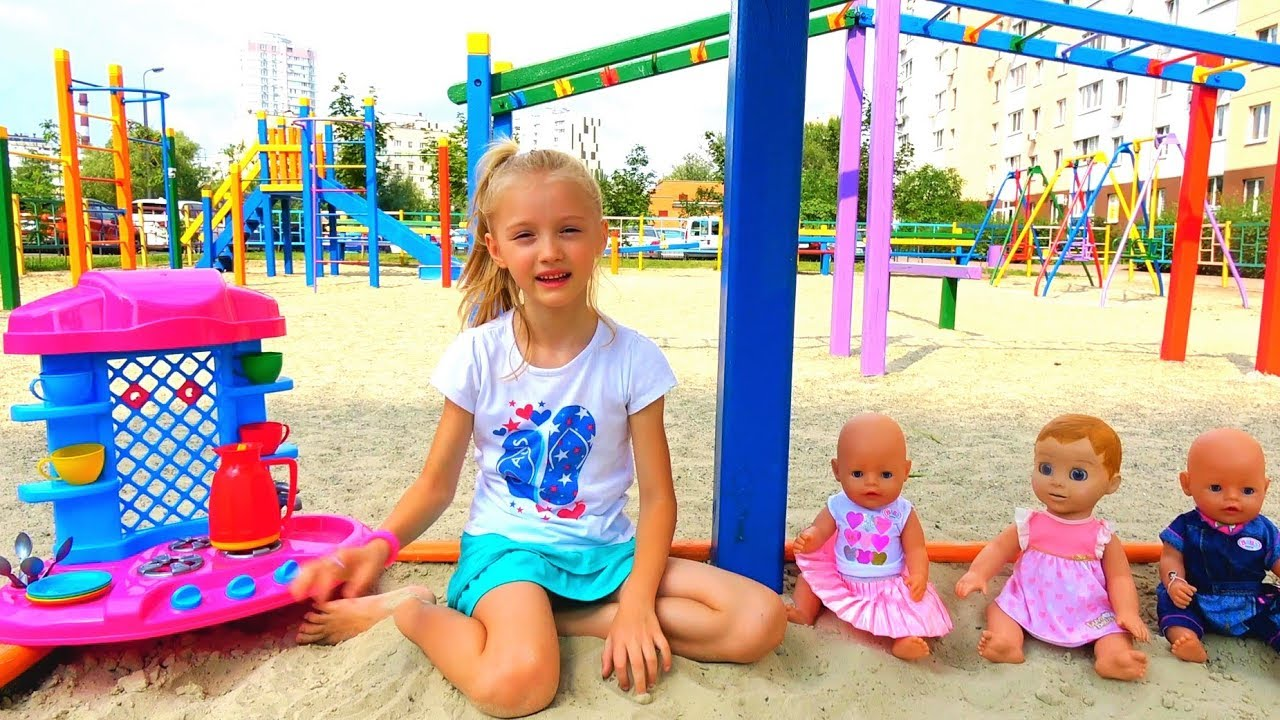 Download Funny Polina playing with Colored cups and baby dolls on the playground