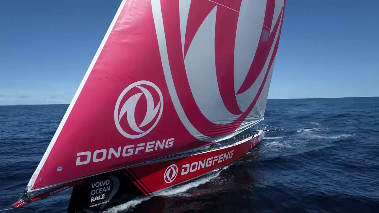 High drone shot of Dongfeng with MAPFRE a half mile astern and to weather. Low drone shot. Both boats under MH0 in light conditions. More drone shots.