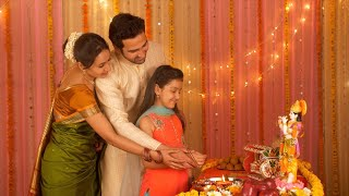 Nuclear Indian family celebrating Janamashtmi at home - Offering prayers to Lord Krishna